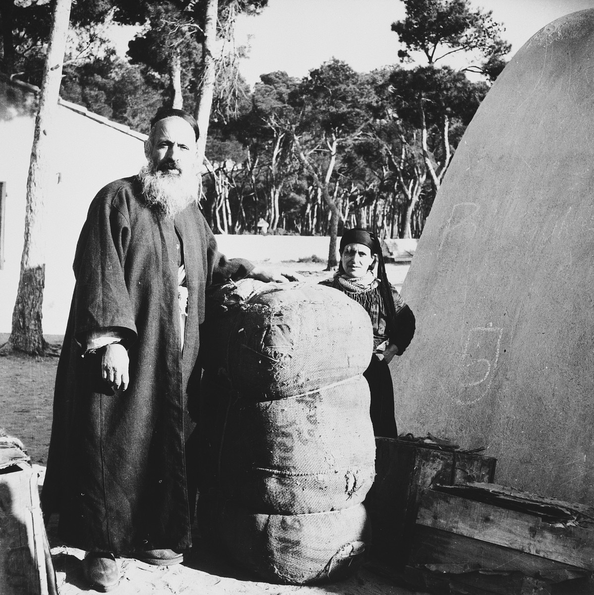 A Morrocan-Jewish man and woman stand next to a large bundle in the Los Arenas camp while waiting to immigrate to Palestine.