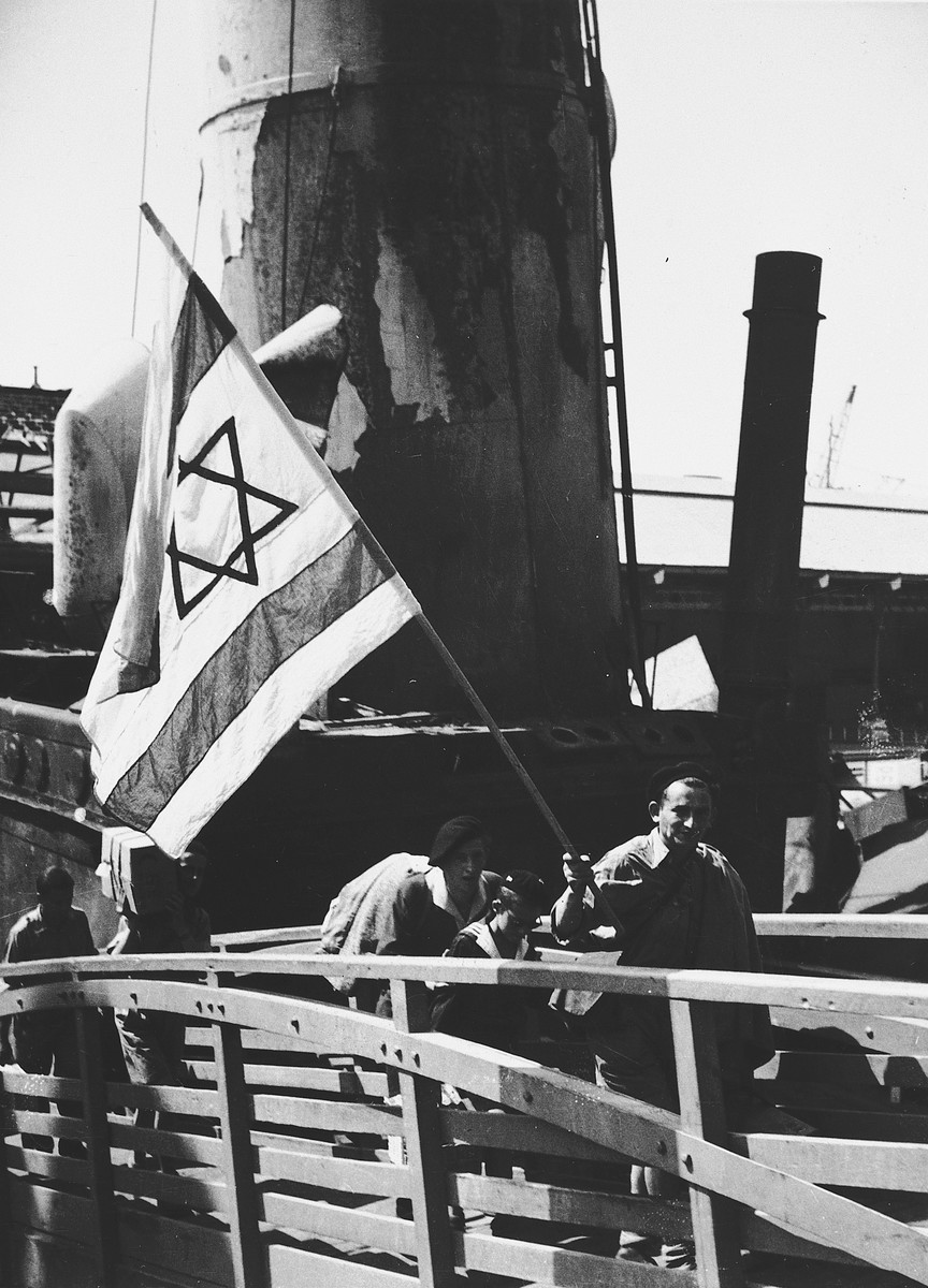Young Holocaust survivors carrying a Zionist flag walk up the gangway to the Mataroa en route to Palestine.