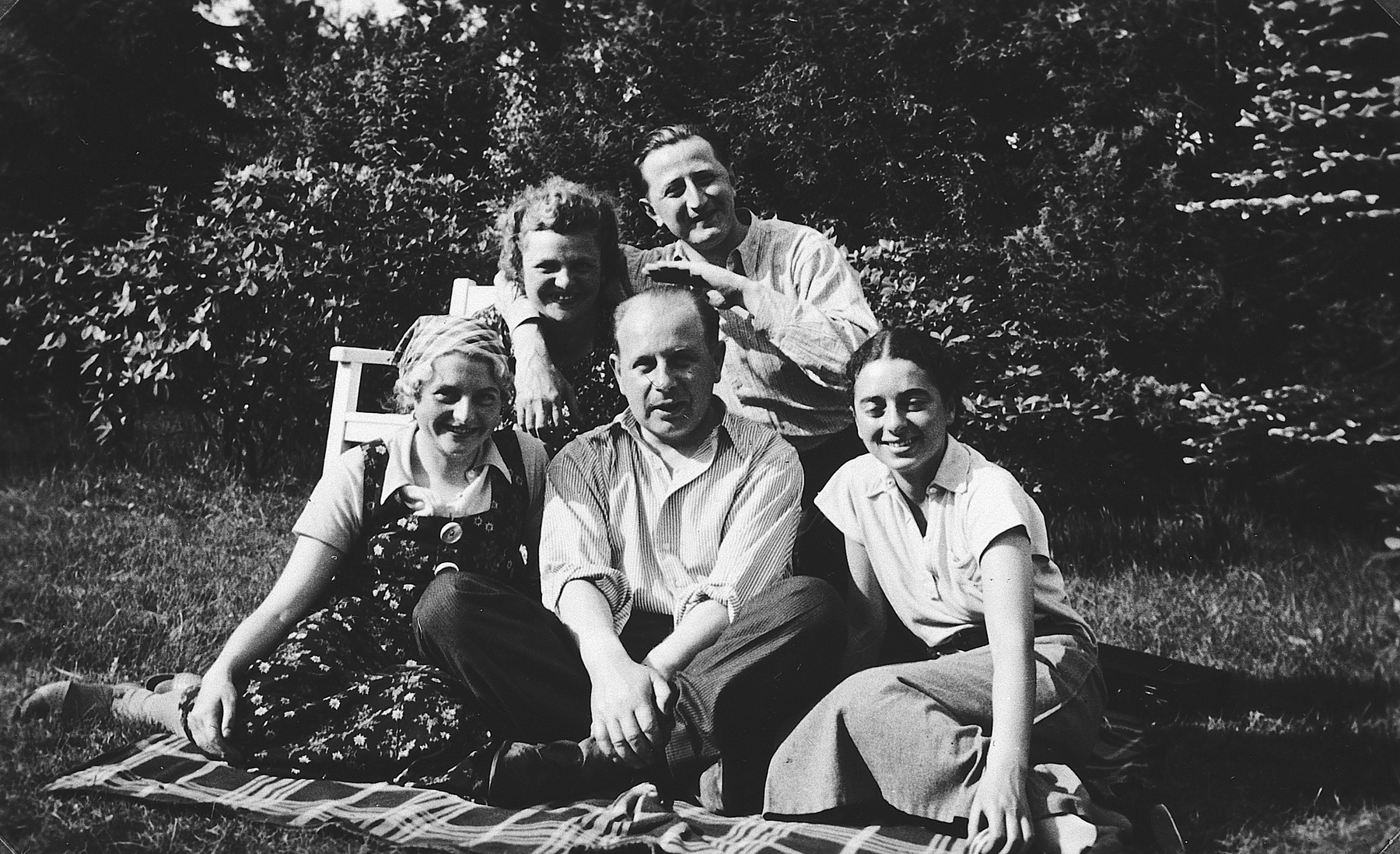 A group of young German-Jewish friends poses for a group portrait on a blanket on the edge of a forest.  Pictured seated on the far right is Margot Bähr.