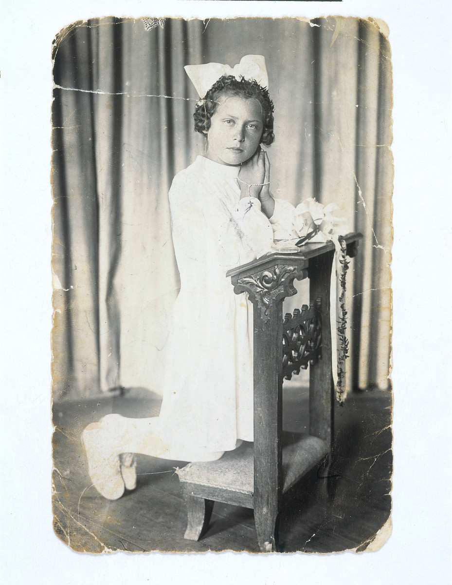 Studio portrait of a Jewish girl in hiding wearing her first communion dress kneeling on a bench with her hands clasped in prayer.  Pictured is Felicja Braun.