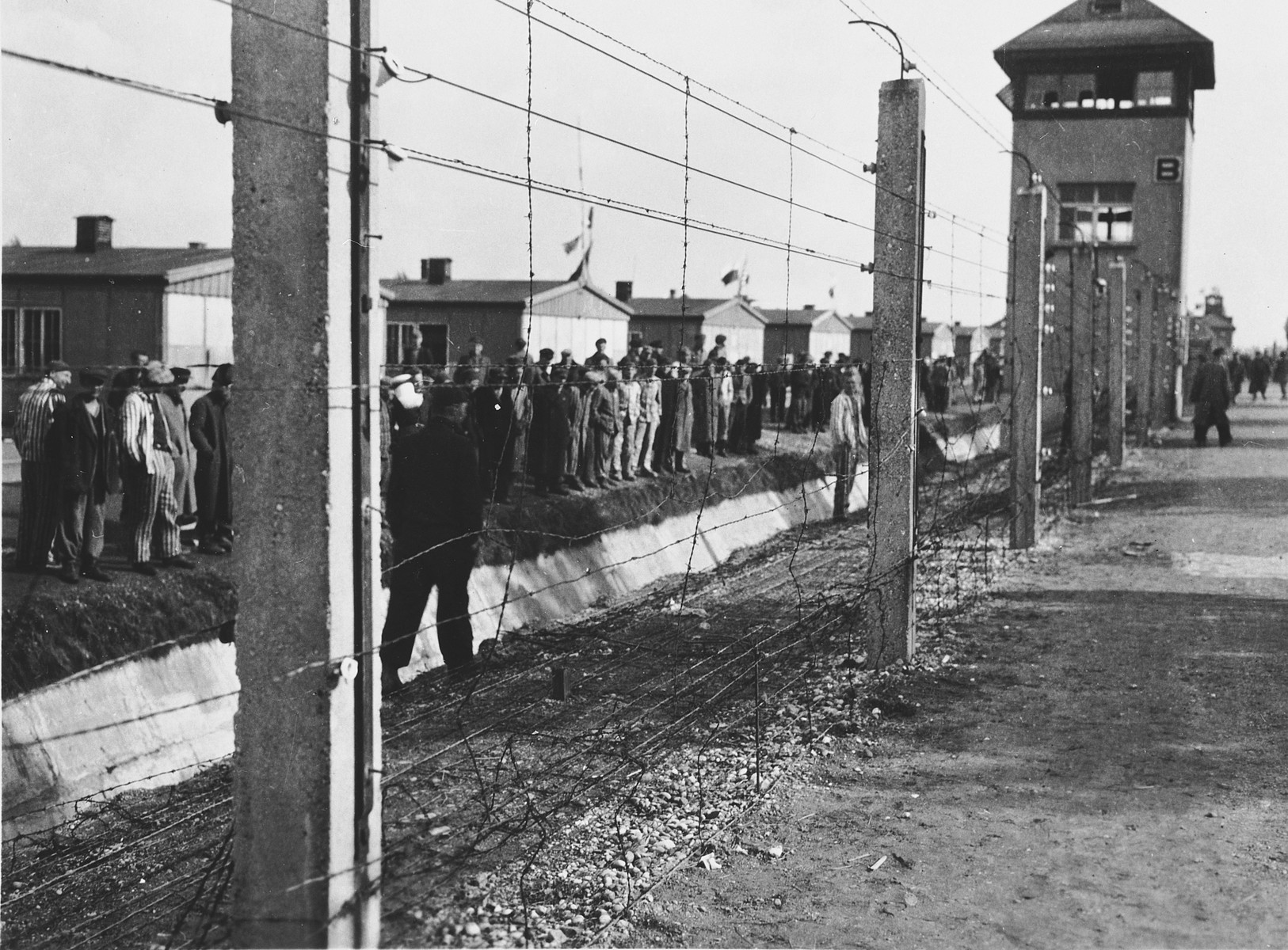 Survivors stand behind the barbed wire fence in Dachau.