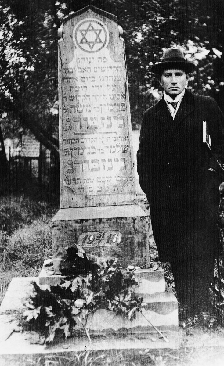 Moise Ginzburg stands next to the grave of his father and uncle, Binyamin and Shlomo Ginzburg, who were killed by bandits on a highway.
