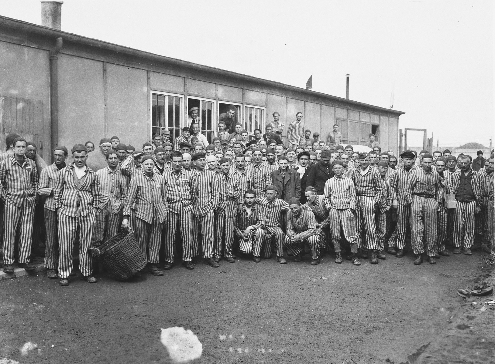 Group portrait of survivors standing in front of a barrack in Dachau after liberation.