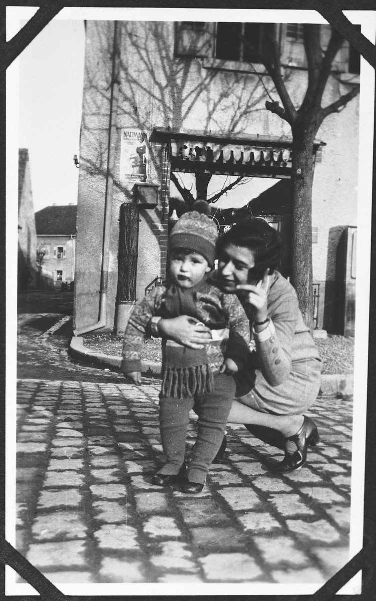 A young mother kneels down next to her toddler daughter to point out something on a cobblestone.  Pictured Ruth Bähr and Horst, [probably relatives from Rimpar].