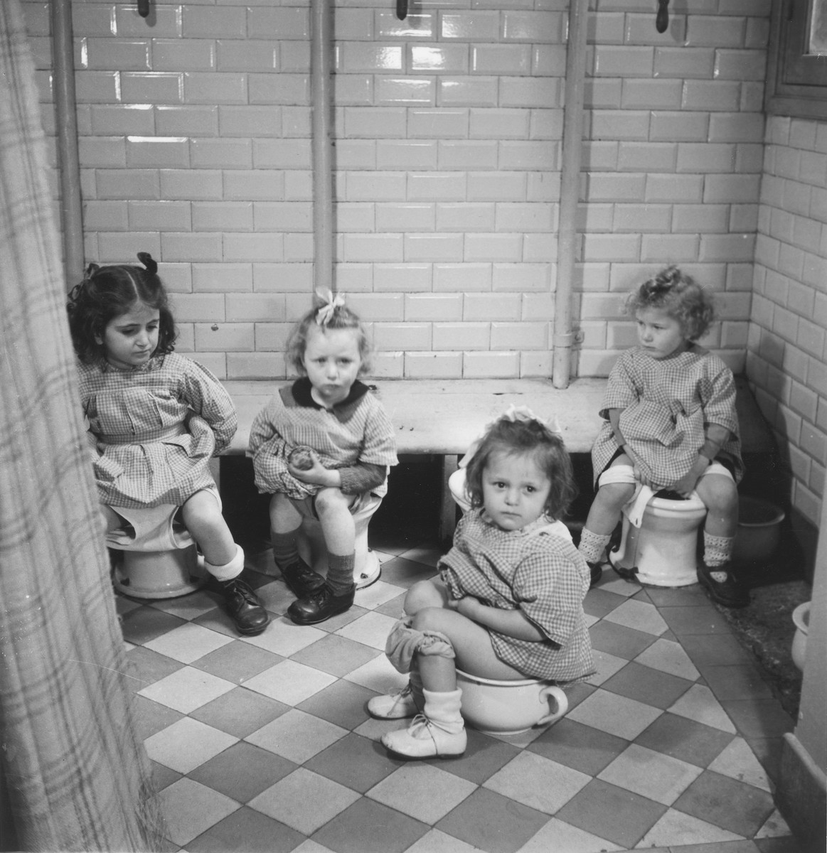 Four little girls sit on the potty in the Petit Monde children's home.