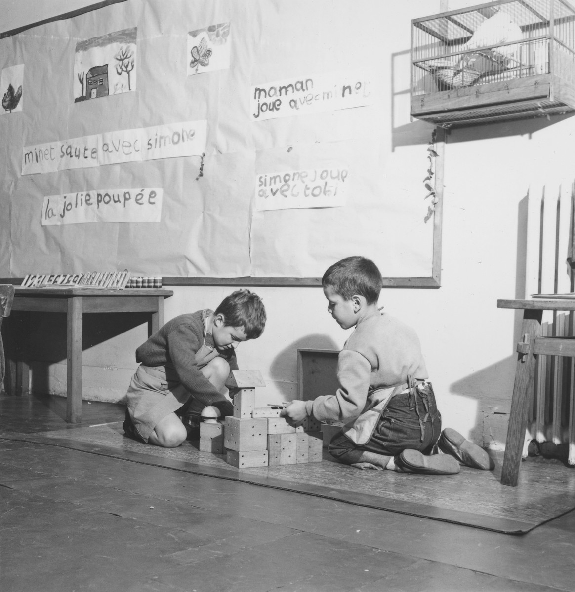 Two young boys sit on the floor underneath a bird cage and build with blocks in a classroom in the Petit Monde children's home.