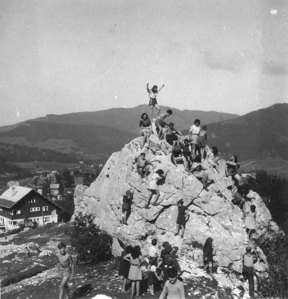 Children scale a large rock in an OSE summer camp.
