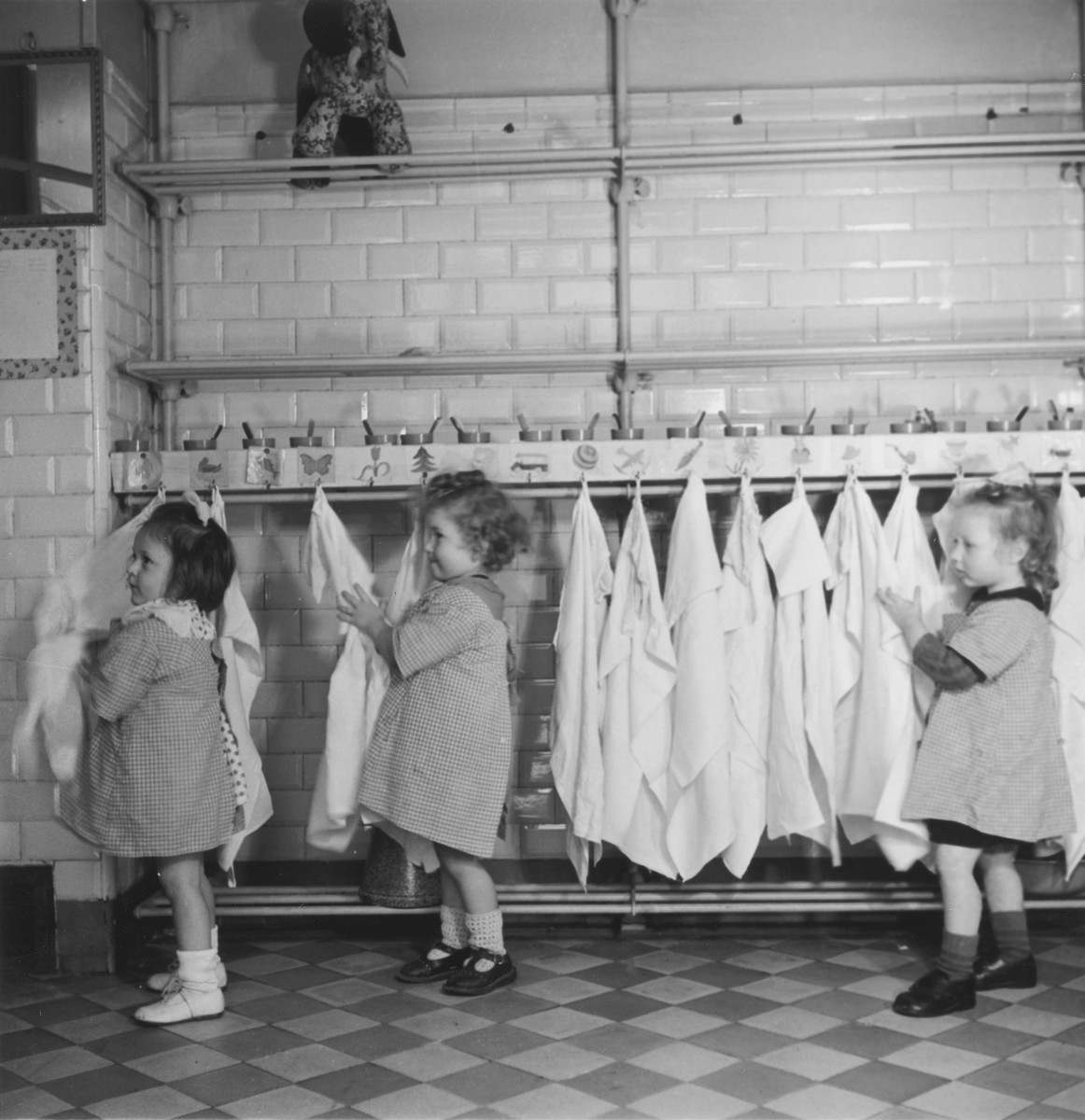 Three little girls dry their hands on towels hanging on hooks in the Petit Monde children's home.