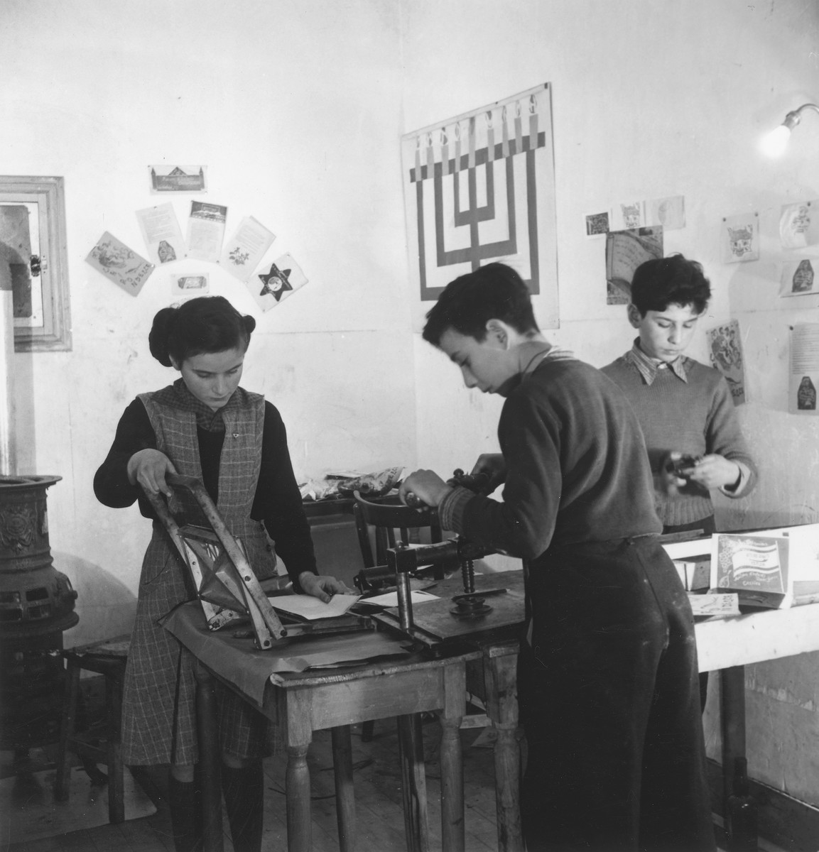 Two boys and a girl make linoleum print greeting cards in an unidentified post-war OSE children's home.