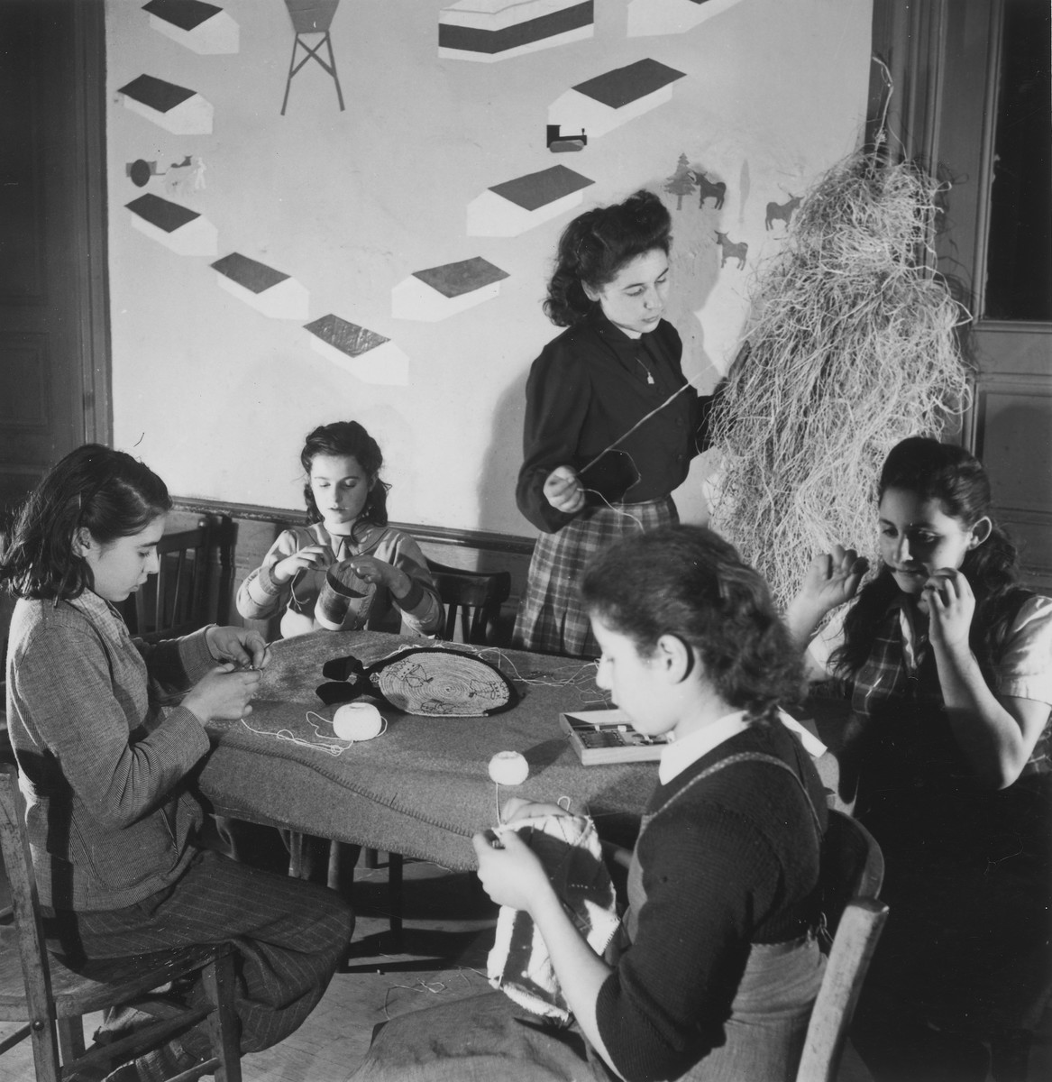 A group of girls makes hand crafts with string in an unidentified post-war OSE children's home.