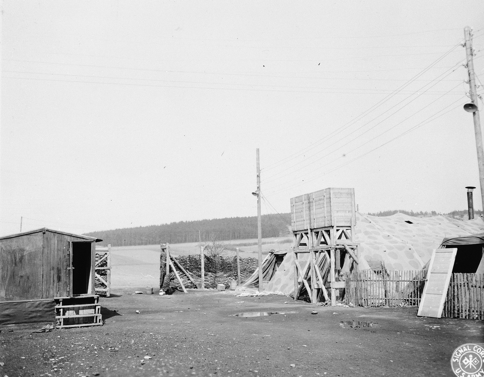 A view of the entrance to the camp.  Prisoners' tents are at right and a small building for camp administrative matters is at the left.