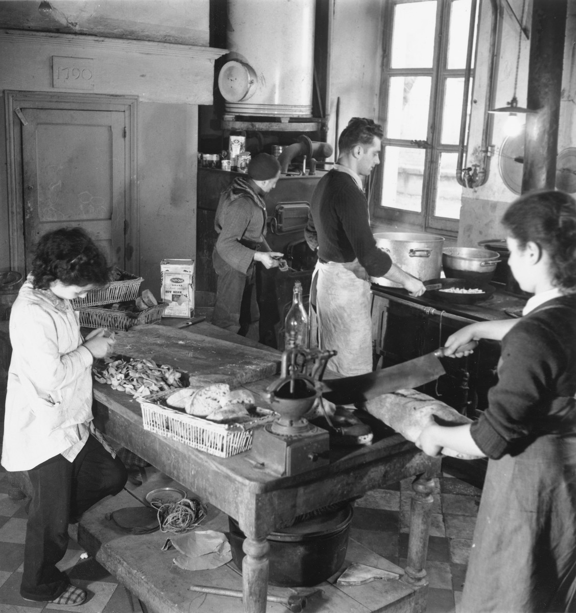 Two children help prepare food in the kitchen of an unidentified post-war OSE children's home.