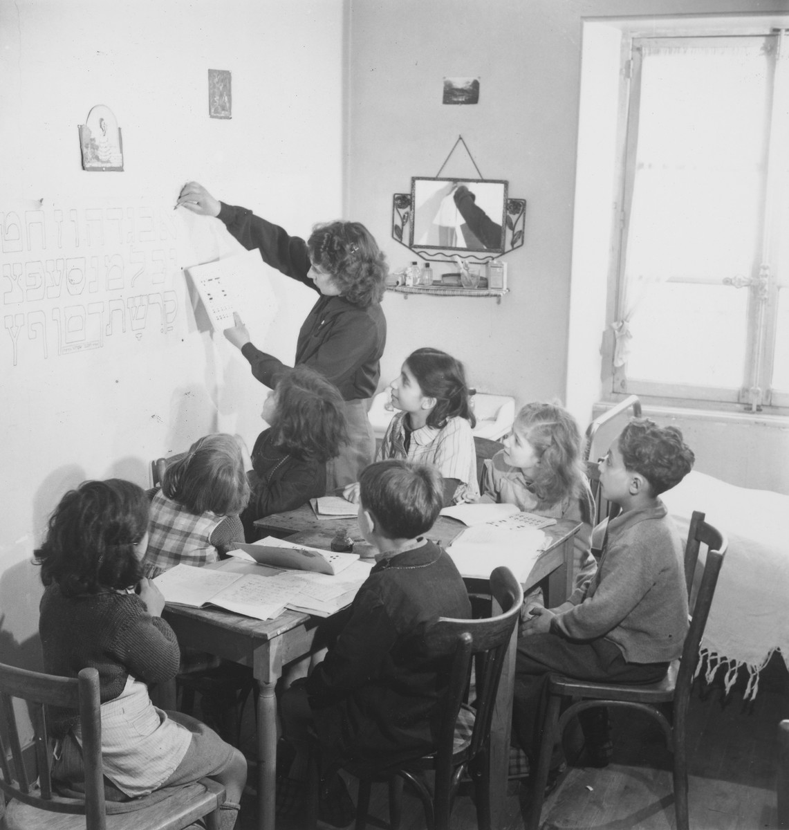 An instructor teaches Hebrew to a group of children seated around a table in an unidentified post-war OSE children's home.