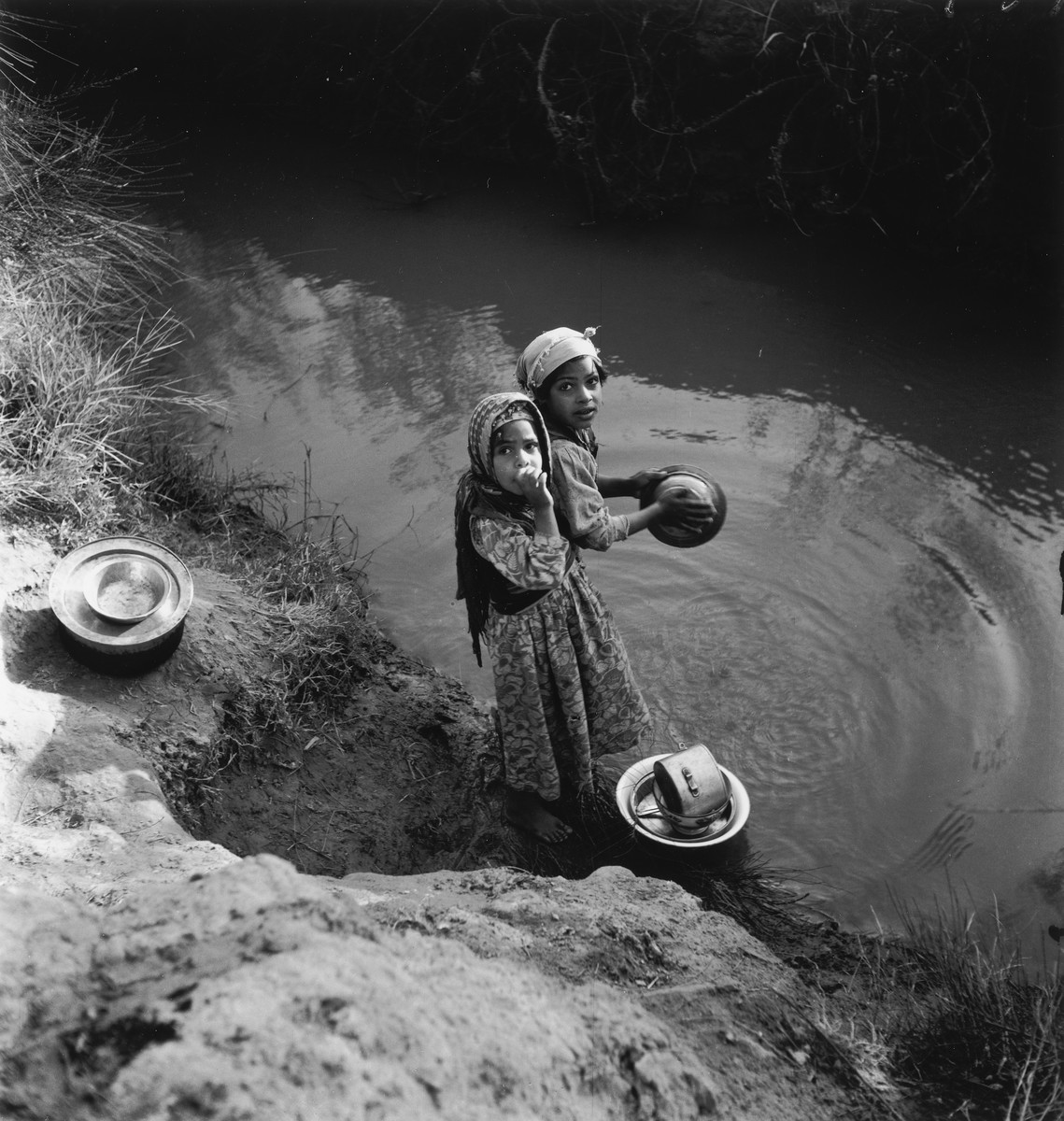 Two Morrocan Jewish girls wash dishes in a lake or river in the Los Arenas camp while waiting to immigrate to Palestine.