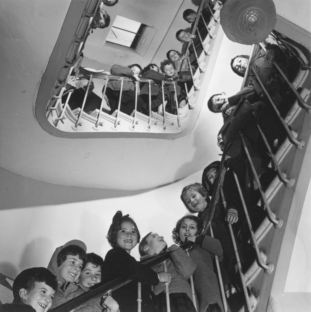 Young children pose for a group photograph on the stairwell of an unidentified OSE post-war children's home.
