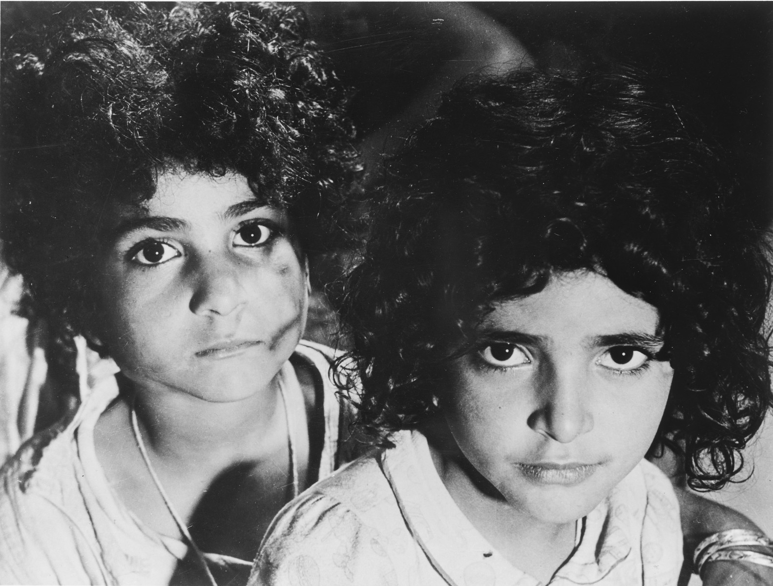 Close-up portrait of two Morrocan Jewish girls in the Los Arenas camp waiting to immigrate to Palestine.