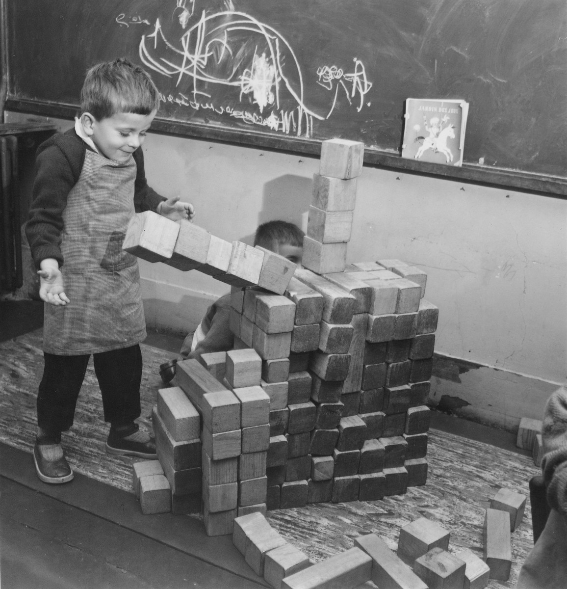 A young boy builds with blocks in a classroom in the Petit Monde children's home.