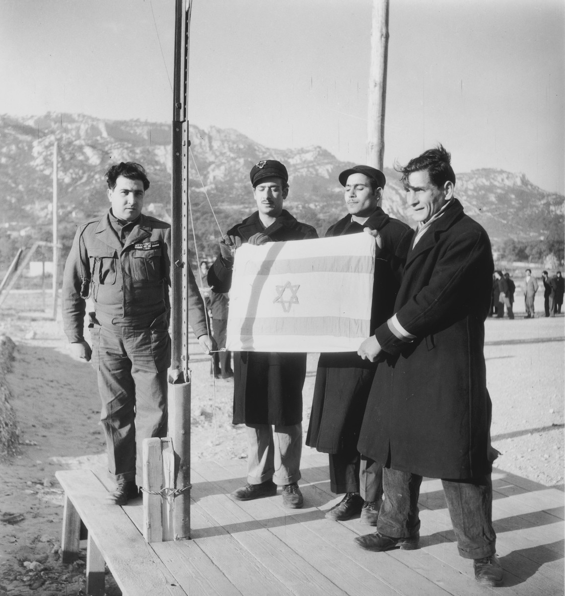 Group portrait of three Jewish displaced persons holding an Israeli flag prior to their departure for Palestine while a soldier looks on.