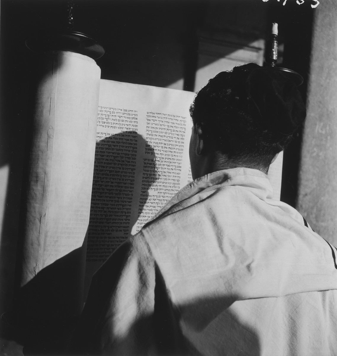 A teenager wrapped in a prayer shawl lifts up the torah scroll during religious services in an unidentified post-war OSE children's home.
