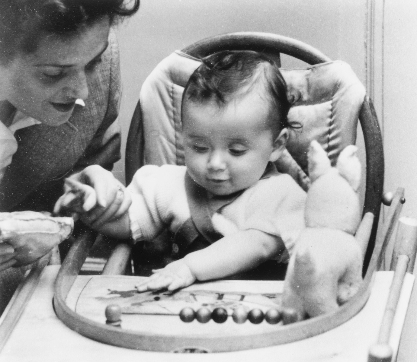 A Dutch-Jewish mother plays with her young baby seated in a high chair.  Pictured are Emmy and Robert Krell.