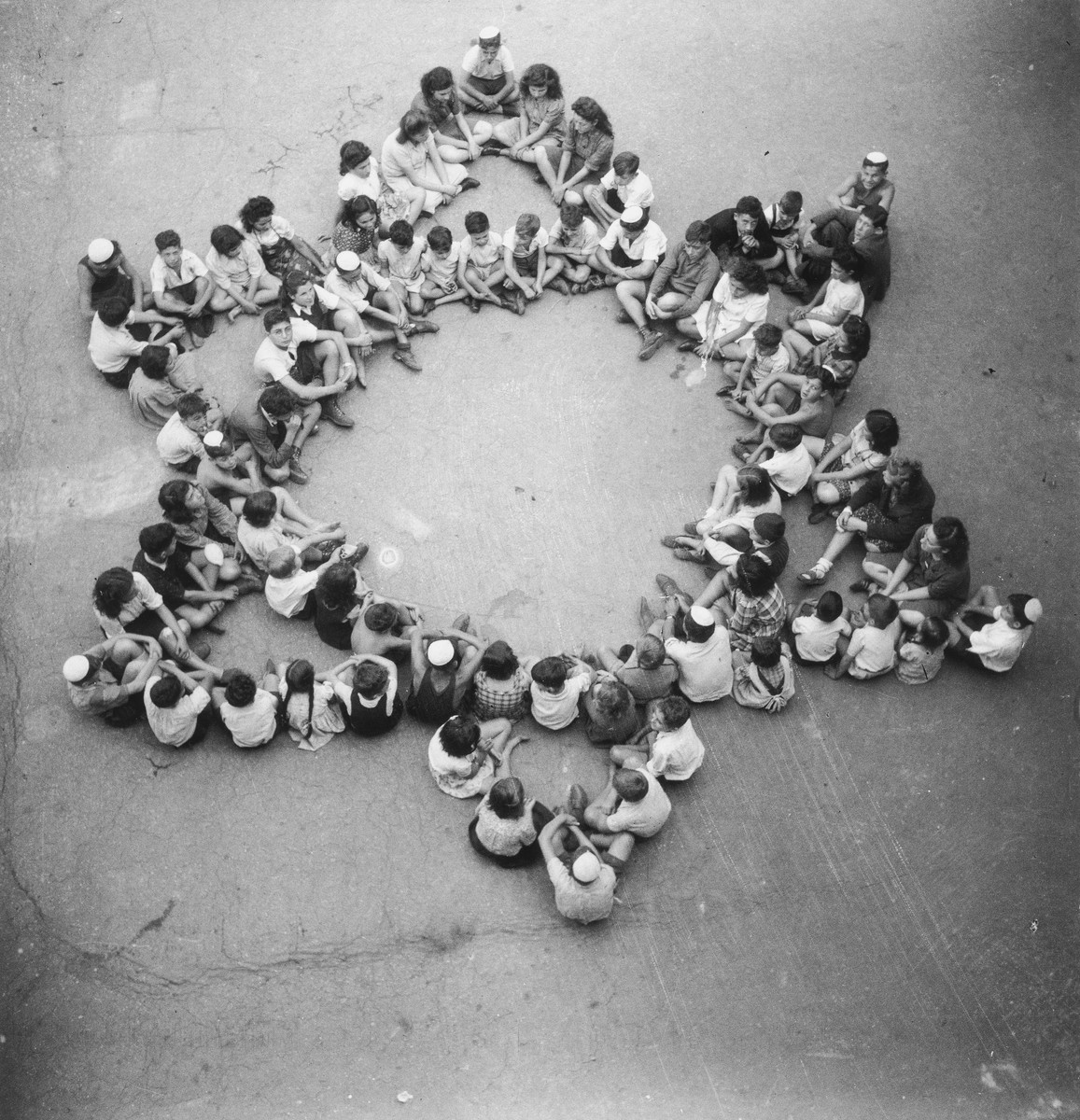 A large group or children sit in a star of David formation in an unidentified post-war OSE children's home.