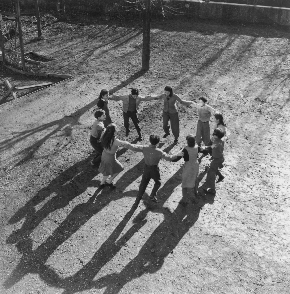 A group of teenagers dances a hora on the grounds of an unidentified post-war OSE children's home.