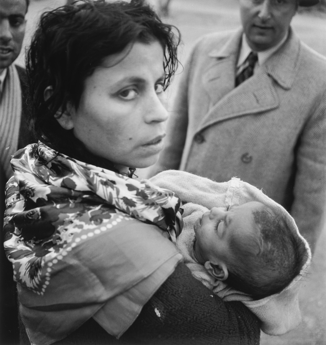 A young Morrocan-Jewish mother cradles her infant in her arms in the Los Arenas camp while waiting to immigrate to Palestine.