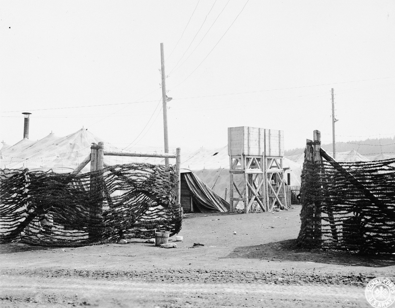 "A view of the entrance to the camp.  Prisoners' tents are at right and a small building for camp administrative matters is at the left.  The original caption reads: ""This picture shows the main and only entrance to the concentration camp inclosure (hereinafter referred to as the Arnstadt Espenfeld Camp.  Artificial strips of grass, ostensibly for camouflage purposes (but probably to preclude a view of the ground in front of the tents from the roadway) drape inclosure entrance and the other part of the inclosure in which prisoners would be visible from the road.  The boxes on props are water tanks.  Hanging near the tank is an iron pipe 8 inches in diameter which was used as a gong signal to awaken and summon the prisoners to the yard."""