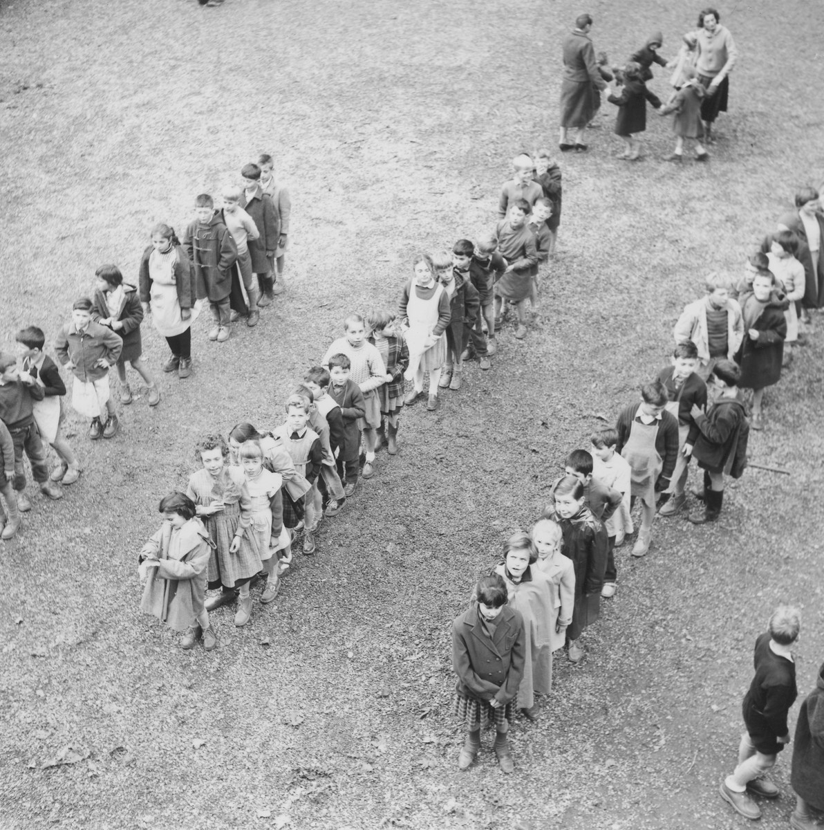 Young children stand in lines in an outdoor field in an unidentified OSE post-war children's home.