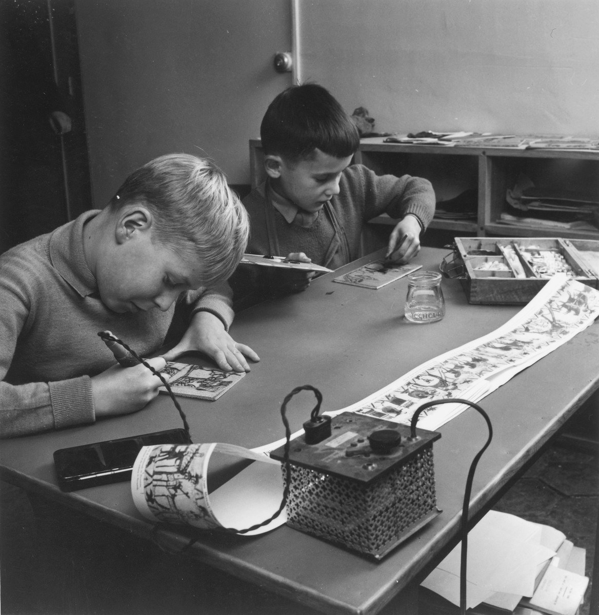 Two boys work on an art project in a classroom of an unidentified OSE post-war children's home.