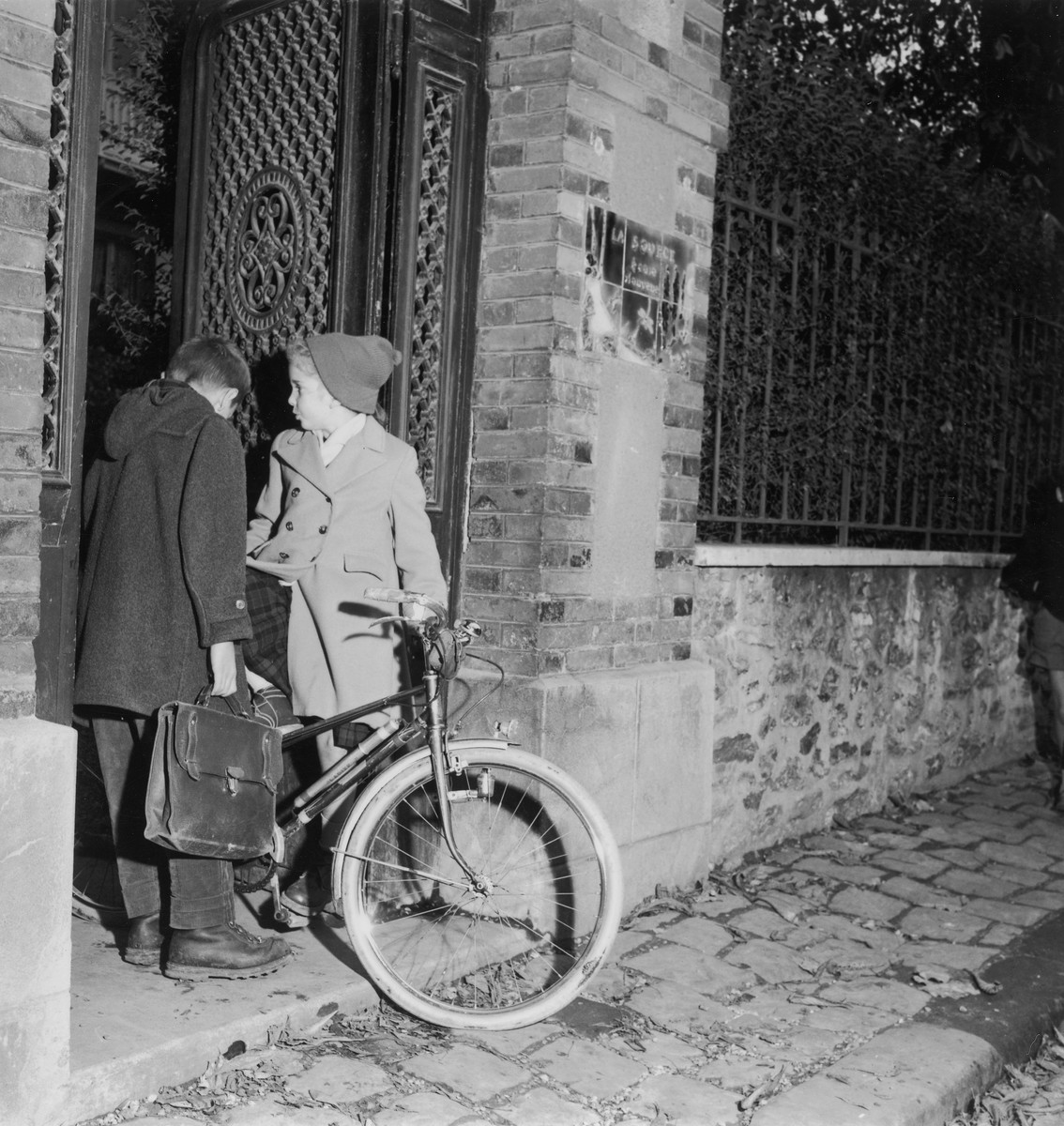"""Two young children, one with a bicycle, stand outside La Source, a progressive school [probably supported by OSE] after the war.    The sign at the gate reads """" La Source:  ecole nouvelle."""""""