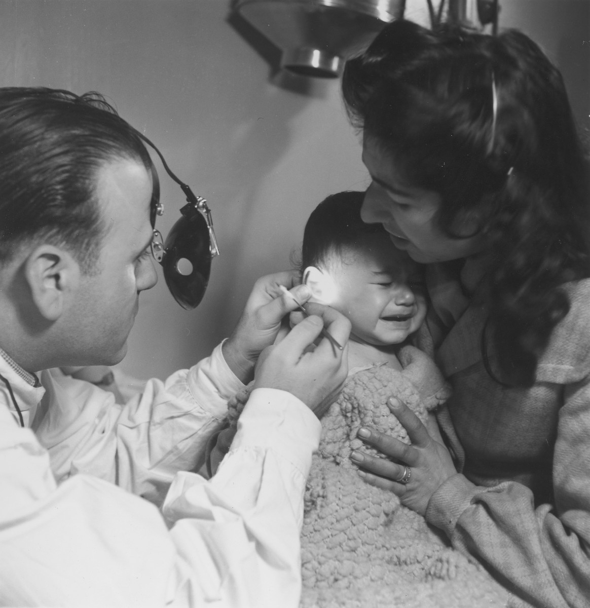 A physician looks into the ear of a sick infant in an OSE health clinic.