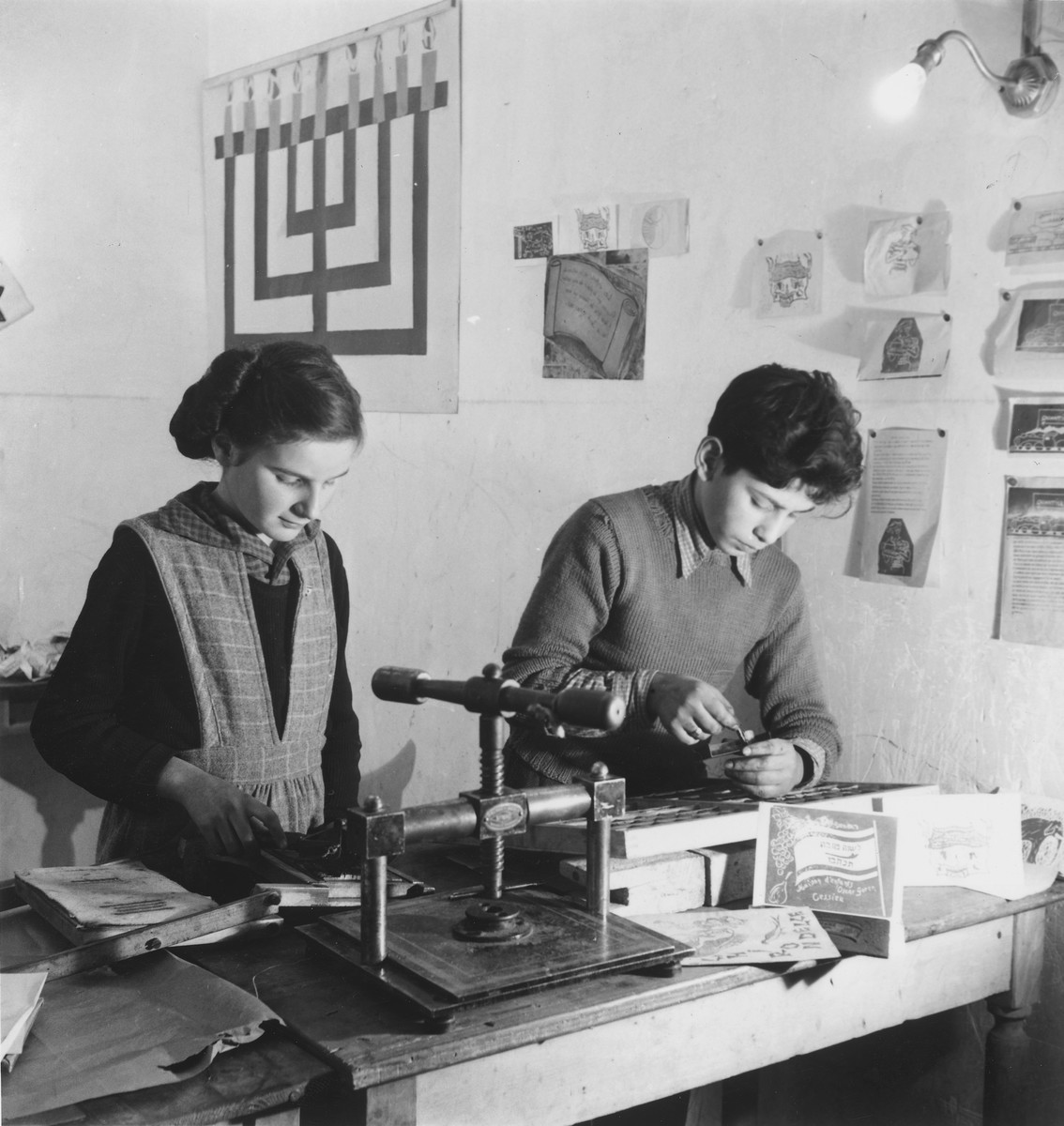 A boy and a girl make linoleum print greeting cards in an unidentified post-war OSE children's home.
