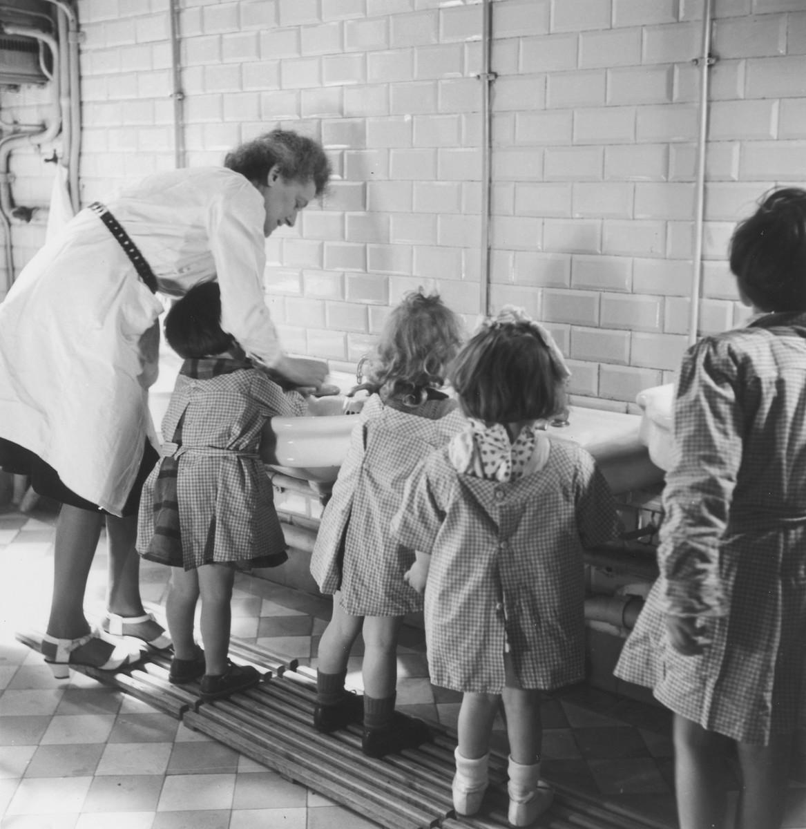 A female caregiver helps a group of little girls to wash their hands in the Petit Monde children's home.