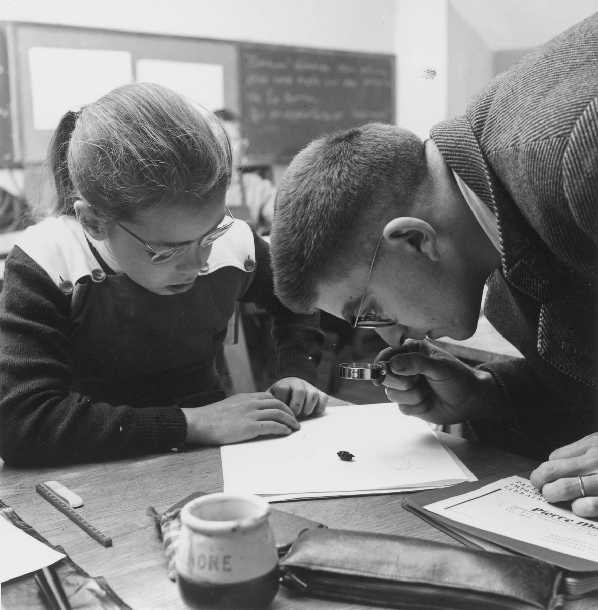 A teacher looks through a magnifying glass while a young girl seated at the table looks on in a classroom of an unidentified OSE post-war children's home.