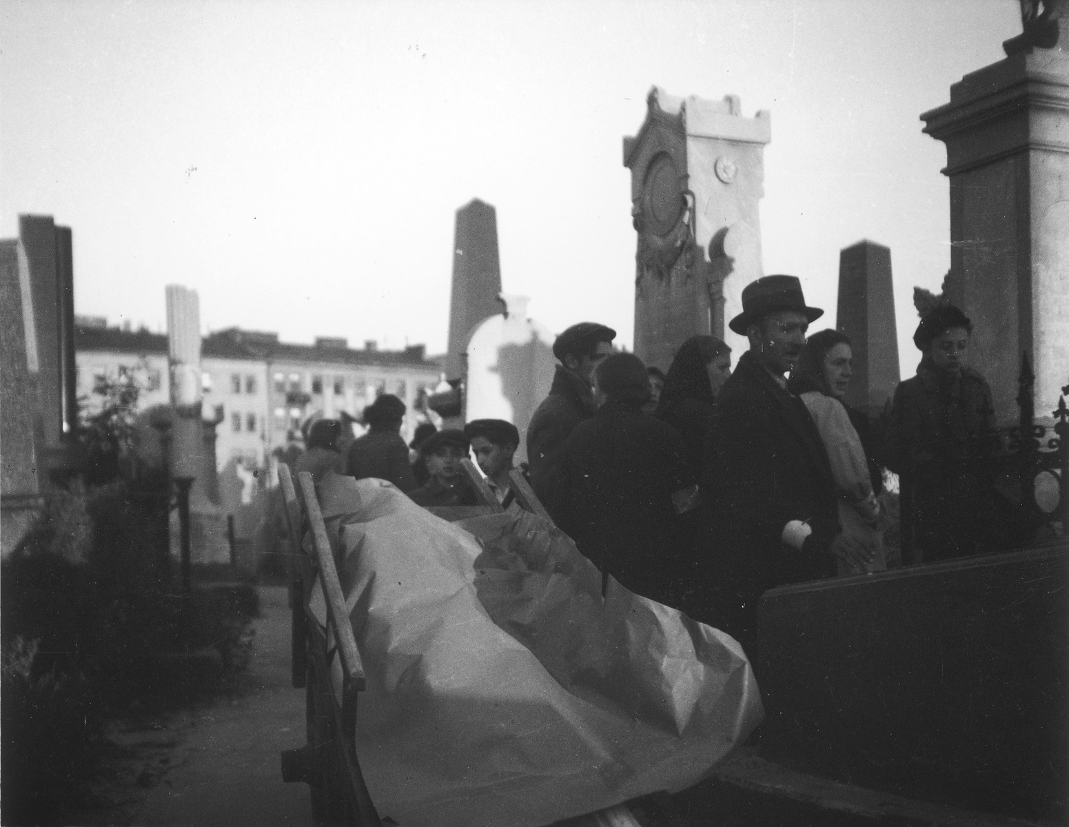 "Ghetto residents attend a funeral service at the Jewish cemetery in Warsaw.  Joest's original caption reads: ""This funeral took place not in the area of the huge mass graves but between the tall funerary columns.  At the graveside a prayer for the dead was recited, the Kaddish."""
