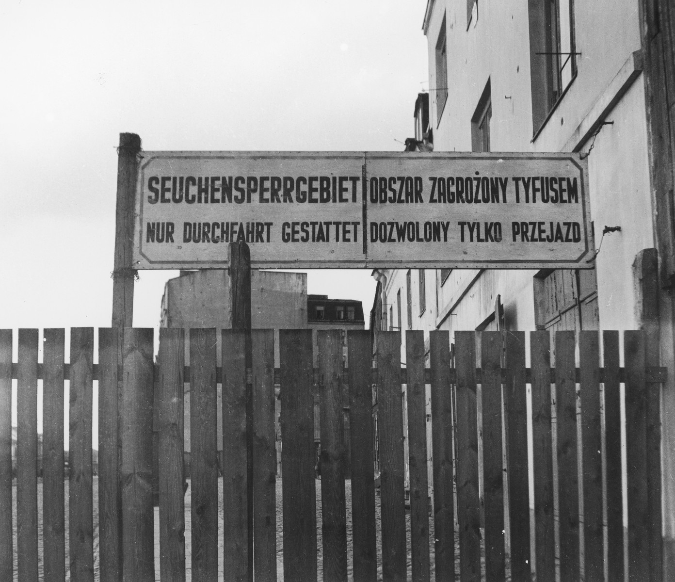 """A sign in German and Polish posted at entrance 2 to the Warsaw ghetto reads, """"Area closed because of epidemic. Only through traffic permitted.""""    Joest's original caption reads: """"No one drew back in fear from the terrifying sign 'Epidemic Quarantine Area' posted at the entrances to the Ghetto.  'Aryan' Poles were allowed to pass through; Jews were not."""""""