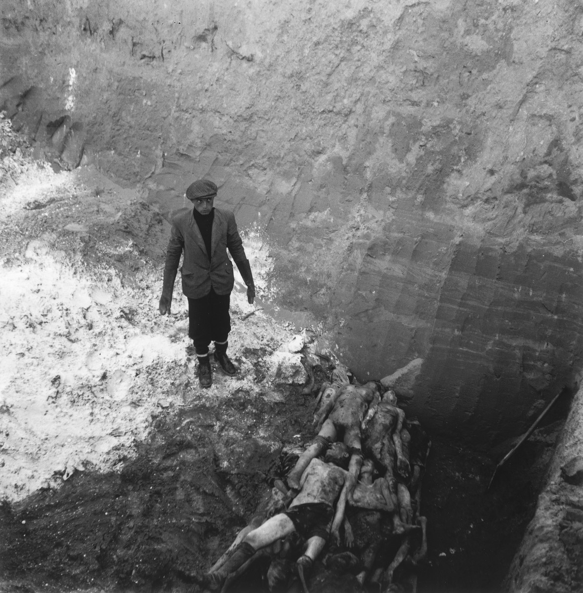 """A laborer at the Jewish cemetery on Okopowa Street buries bodies in a mass grave.  Joest's original caption reads: """"The man down below stood on the lime.  He had to place the corpses as close together as possible to save space."""""""