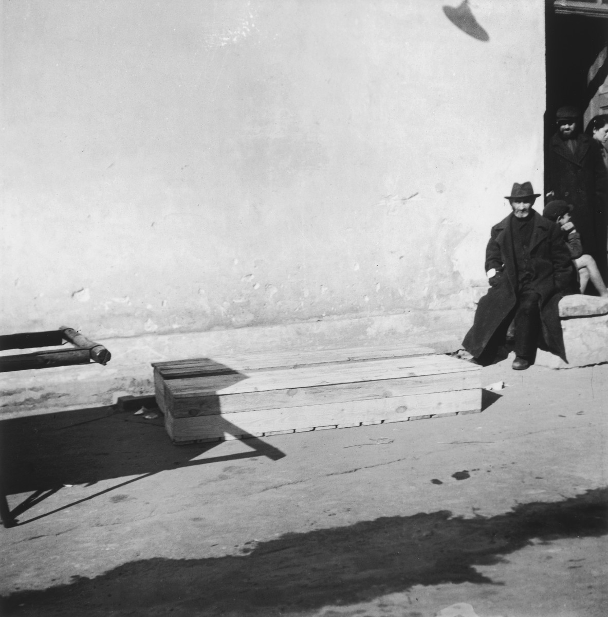"A man sits and waits for the burial of two relatives in the Warsaw ghetto cemetery.  Joest's original caption reads: ""Two wooden boxes with corpses were waiting to be buried, and in the background the relatives were waiting as well."""