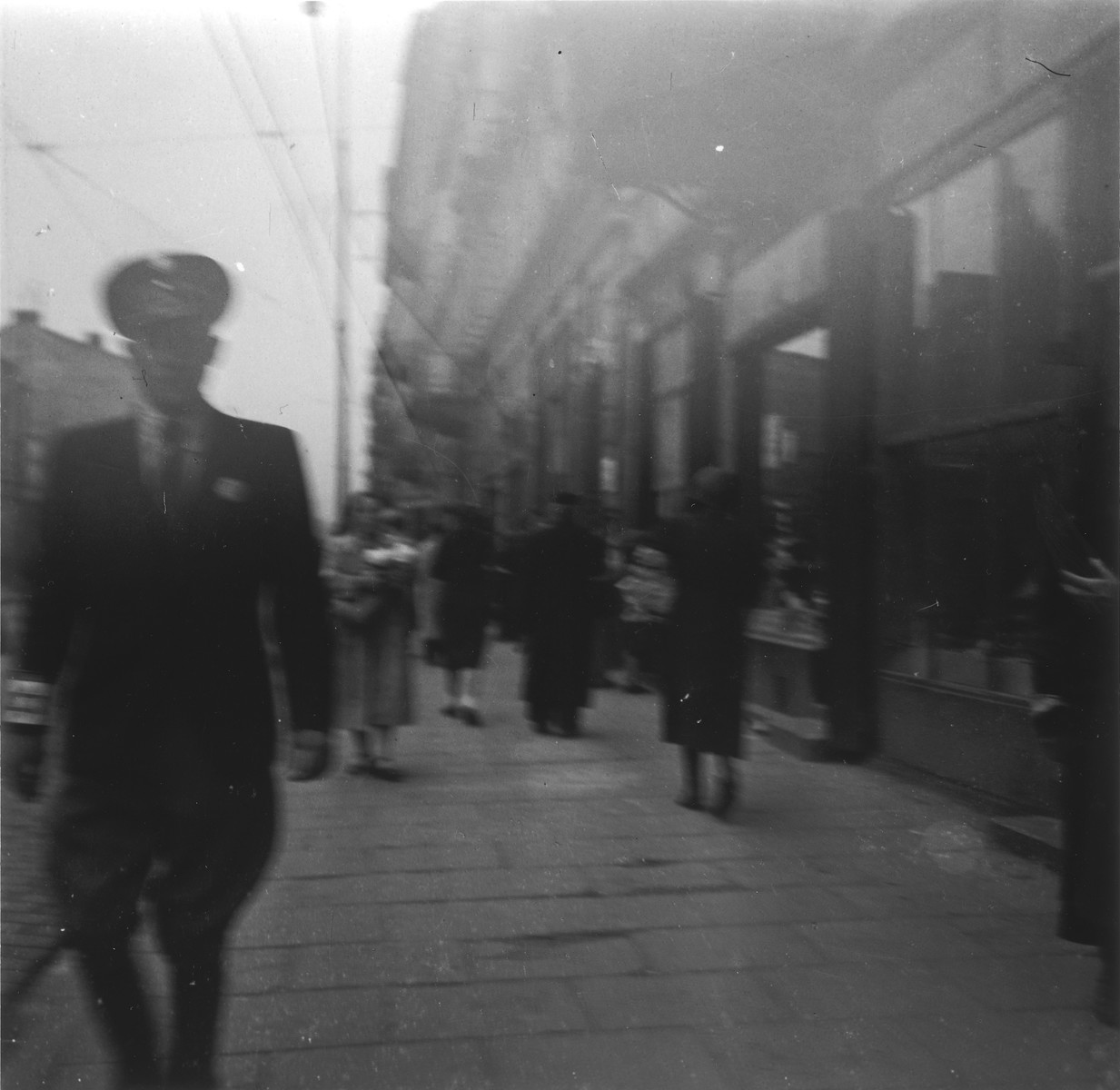 """A Jewish policeman walks down the street in the Warsaw ghetto.  Joest's original caption reads: """"That was a man from the Jewish police.  Most of the people avoided him just as they did the German soldiers, although the policemen only had rubber clubs and the soldiers had guns.  On this day, however, I heard no shots."""""""