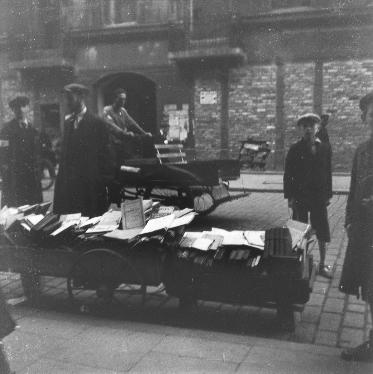 "A vendor sells used books on a street in the Warsaw ghetto.  Joest's original caption reads: ""A book cart with sheet music, old books, collected works tied together.  I was astonished by how often passers-by stood here to leaf through the books or to read."""