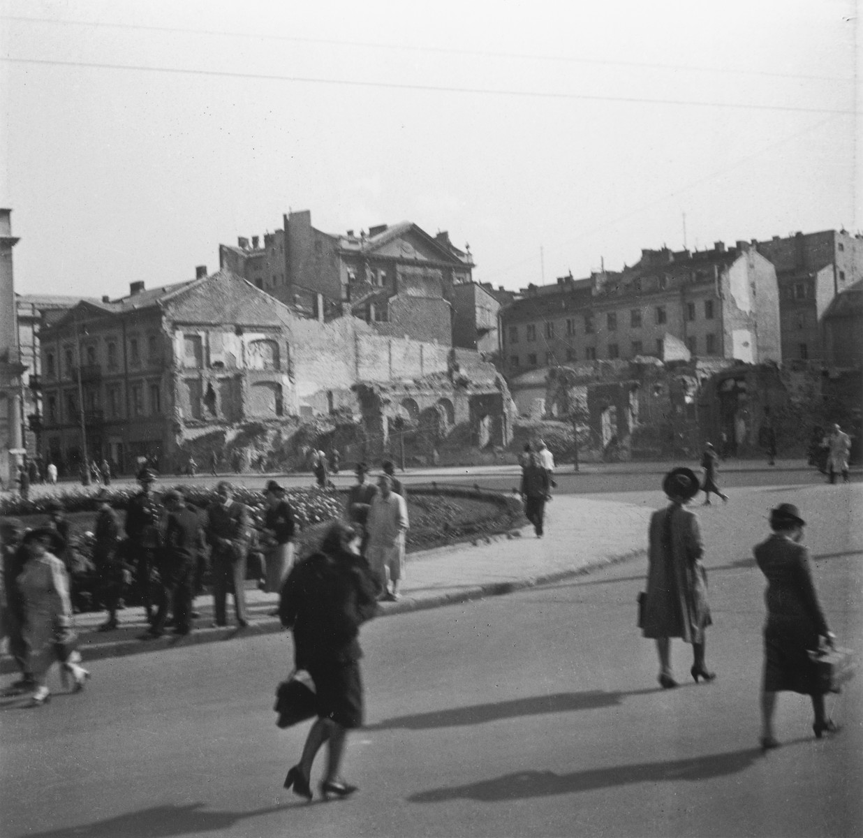 "Street scene in Warsaw, possibly in the ghetto.  Joest's original caption reads: ""I no longer know if this was still in the Ghetto or outside.  No one is wearing armbands with the Star of David; on the footpath is a German police officer."""