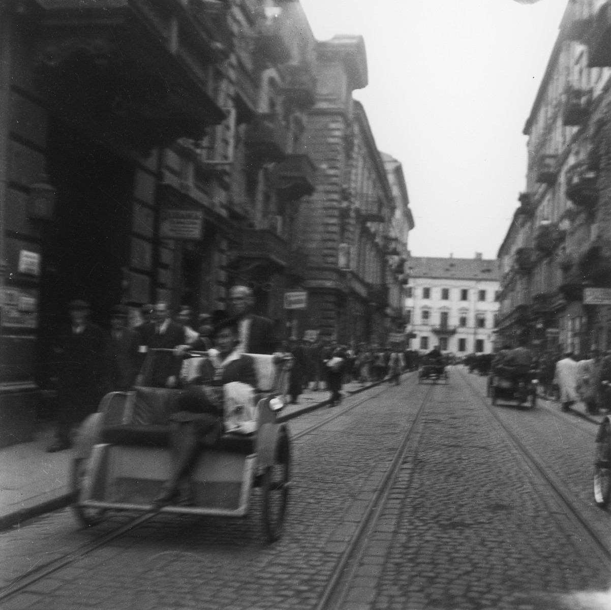 "A Jewish woman rides in a rickshaw down Karmelicka Street in the Warsaw ghetto.  Joest's original caption reads: ""Likewise in Karmelicka Street.  Almost no one walked in the street, everyone was on the sidewalks.  A few people were quite well-dressed."""