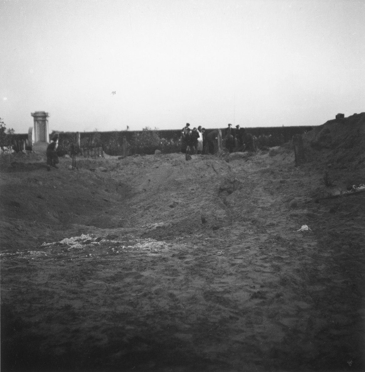 "Residents of the Warsaw ghetto attend a funeral in the ghetto cemetery.  In the foreground is a mass grave that has just been covered over.  Joest's original caption reads: ""This huge grave pit had just been covered over.  The earth was still settling and had fissures in it.  In the background a funeral for an individual grave was taking place."""