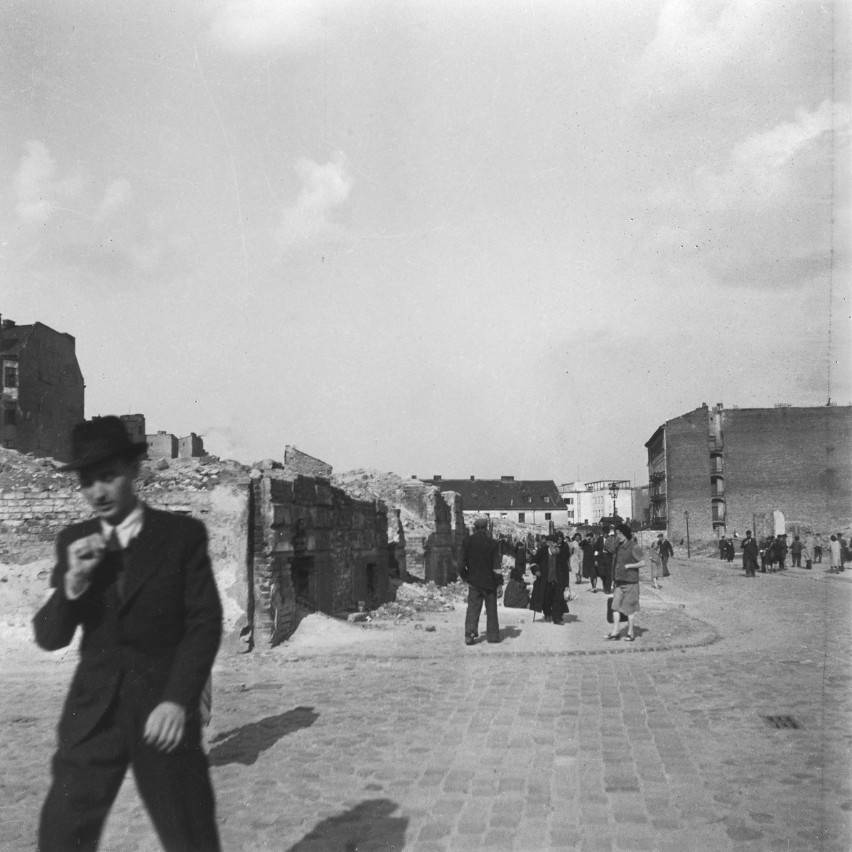 """Local inhabitants walk through the bombed-out streets of the Warsaw ghetto.  Joest's original caption reads: """"I don't know where this was.  It was quite normal to see many people in the bombed-out streets of Warsaw."""""""