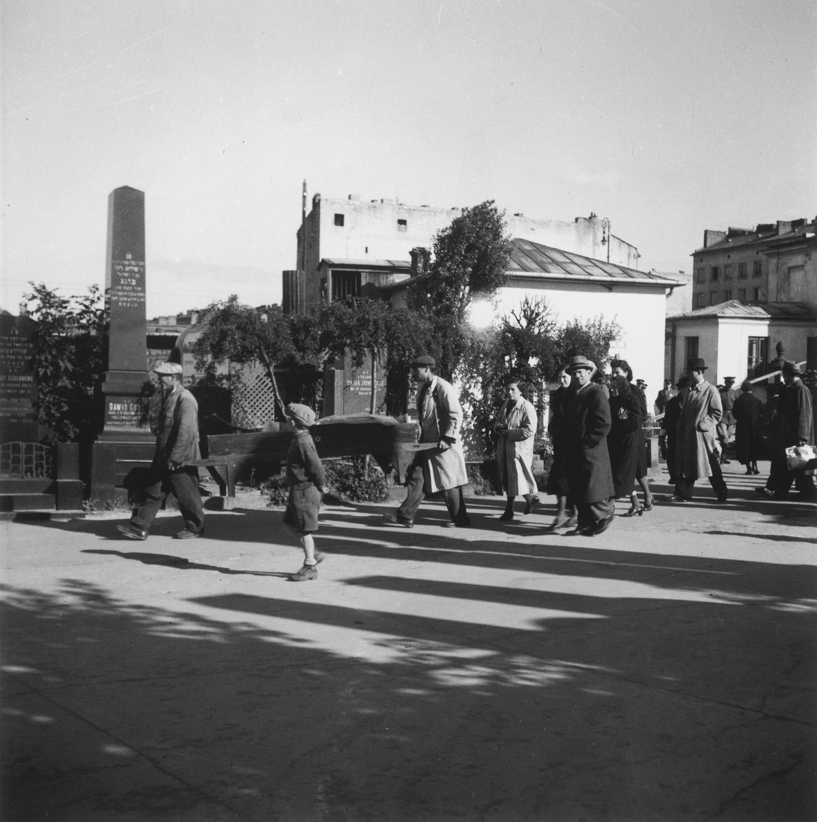 """A burial procession in the Warsaw ghetto cemetery.  Joest's original caption reads: """"This was a 'better' sort of funeral.  The corpse was not put on a car but was carried wrapped in a shroud.  A small procession of relatives followed behind.  Evidently a well-do-do family - up to that point."""""""