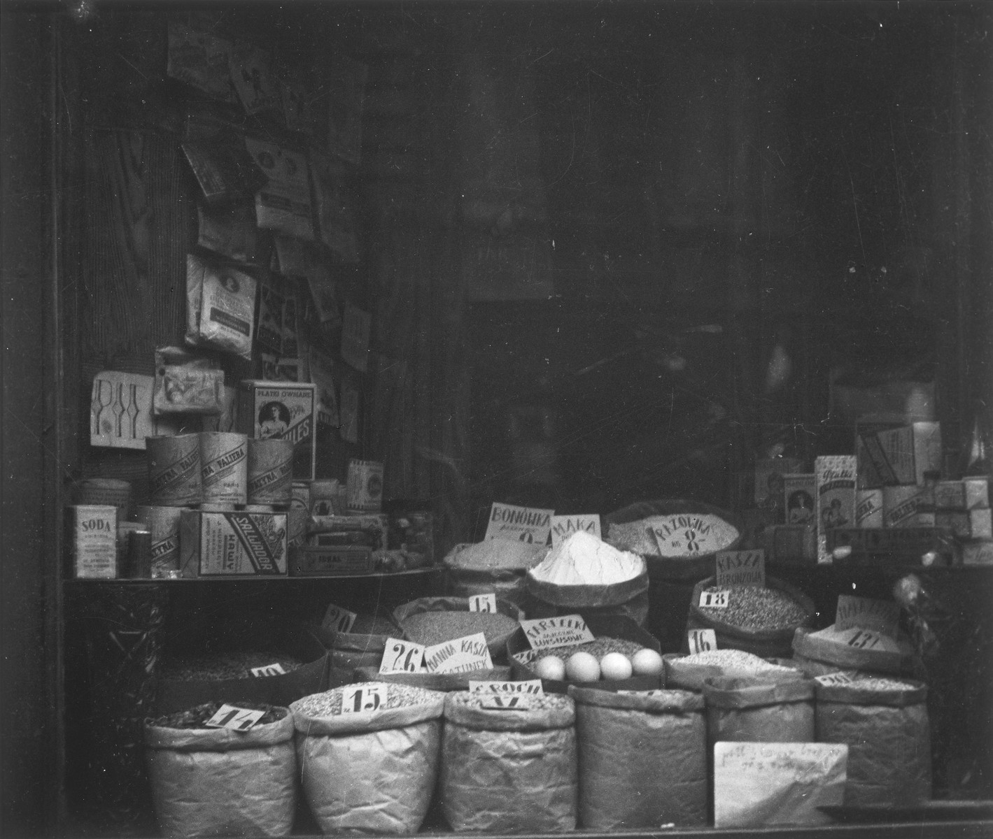 "Close-up of a shop window in the Warsaw ghetto.  Joest's original caption reads: ""In the window there were beans, grits, legumes, salt.  Eggs were laid out there, even a pack of coffee, but I didn't know if it was empty.  I never saw any shoppers."""