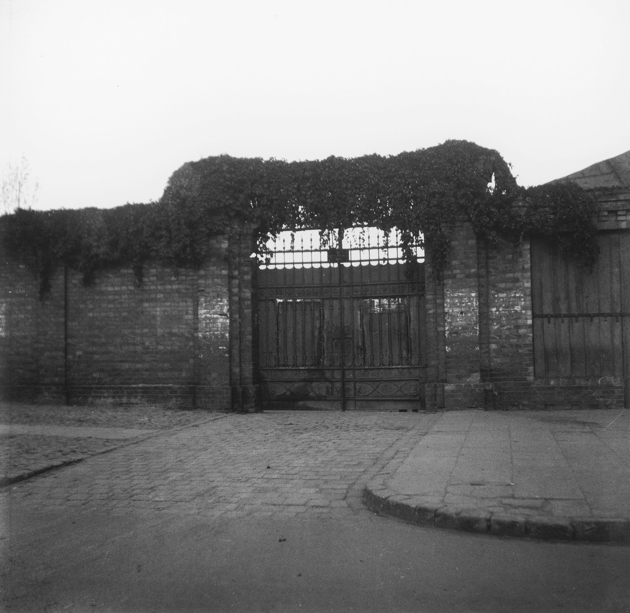 "Entrance to the Warsaw ghetto cemetery.  Joest's original caption reads: ""The gate for entering the Jewish cemetery looked idyllic with its clusters of ivy.  As I stood before it, I had no idea of what I would see beyond it."""