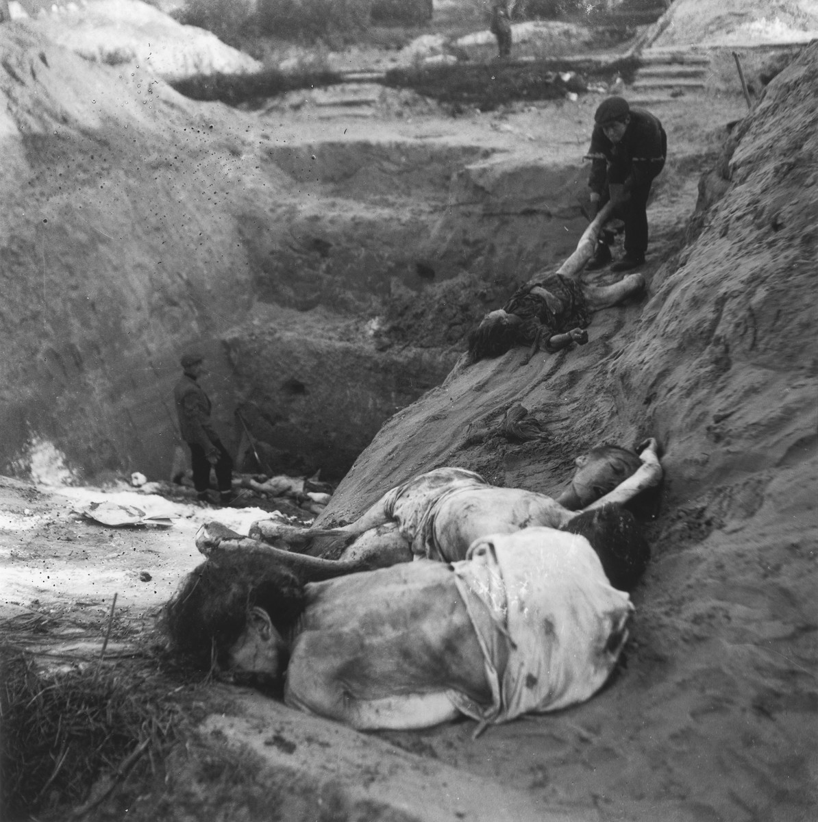 "Laborers at the Jewish cemetery on Okopowa Street bury bodies in a mass grave.  Joest's original caption reads: ""Then he let the corpses slide over the edge down into the pit to the man below, who stacked them next to each other."""