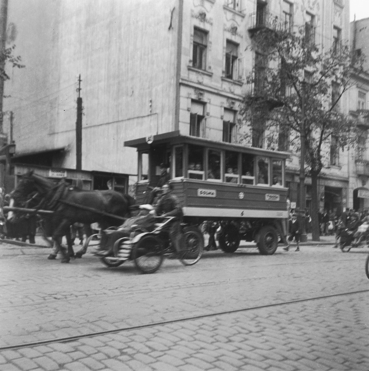 """Horse-drawn streetcars and rickshaws ride down a street in the Warsaw ghetto.   Joest's original caption reads: """"There were horse-drawn streetcars, and there were the rickshaws.  They were faster, but they were almost more expensive, I was told."""""""